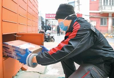 今年2月份,防疫期间,在北京市海淀区中关村街道科育社区内,快递员将快递放入智能快递柜。新华社记者 任 超 摄